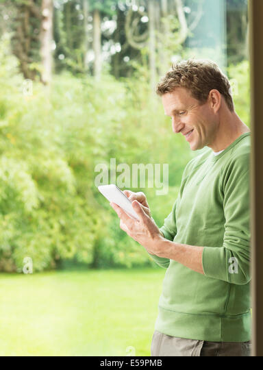 Man using digital tablet by window - Stock Image