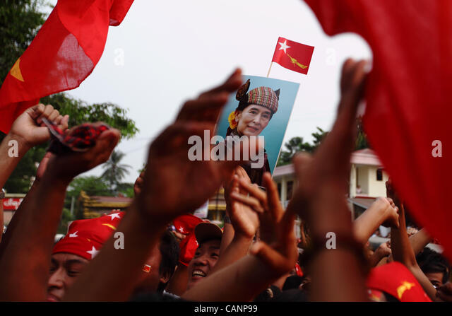 People celebrate at the headquarters of National League for Democracy, waving flags and posters of democracy icon - Stock-Bilder