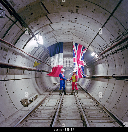 In a Channel Tunnel rail tunnel, a French and UK engineer commemorate the first linking of the two countries since - Stock Image