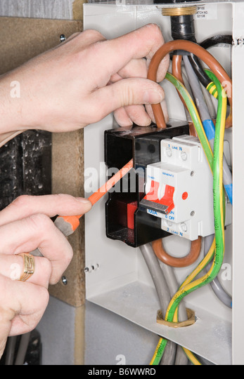 An electrician fixing a fuse box - Stock Image