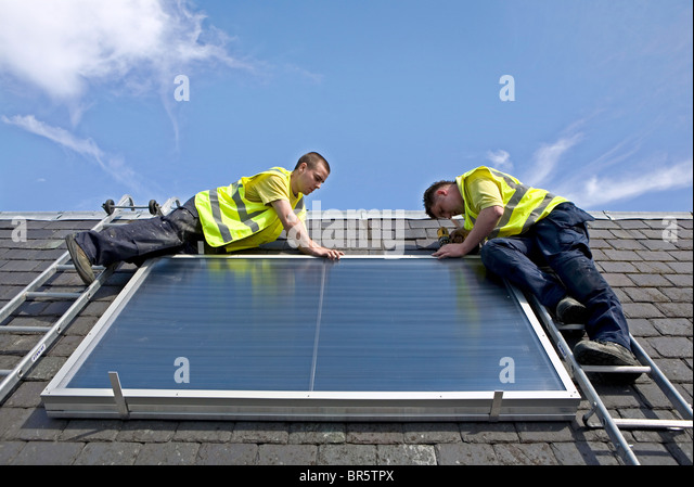 Workmen installing a solar thermal panel on a rooftop. - Stock Image