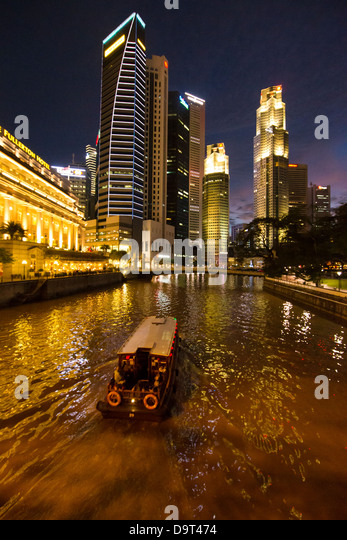the Cavenagh Bridge, a boat on the Singapore River, the Fullerton Hotel and Central Business District at night, - Stock Image