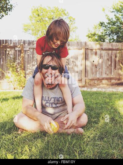 Happy Father And Son Relaxing On Grassy Field - Stock Image