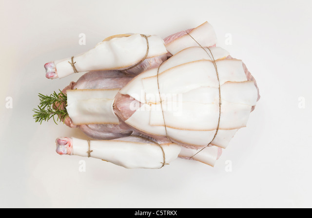 Raw Turkey with bacon slices, elevated view - Stock Image