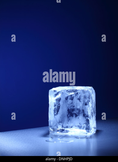 A large square cube / block of ice slowly melting. - Stock Image