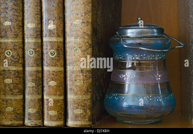 old glass jar with metal lid along with some old books - Stock Image
