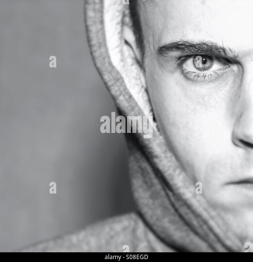 Angry male portrait, half of models face with copy space - Stock Image
