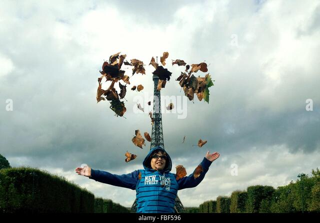 Low Angle View Of Boy Throwing Leaves While Standing Against Eiffel Tower - Stock Image