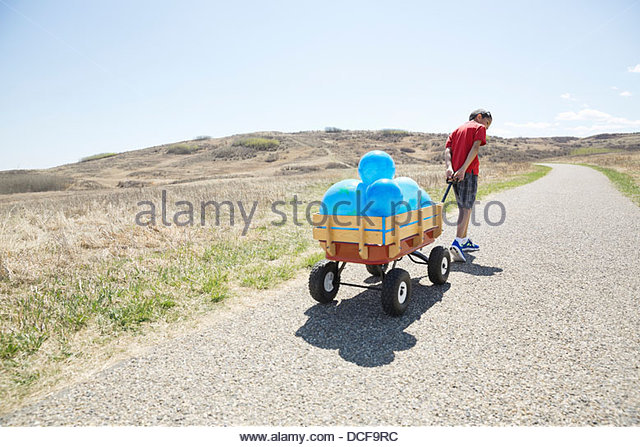Little boy pulling cart full of balloons - Stock Image