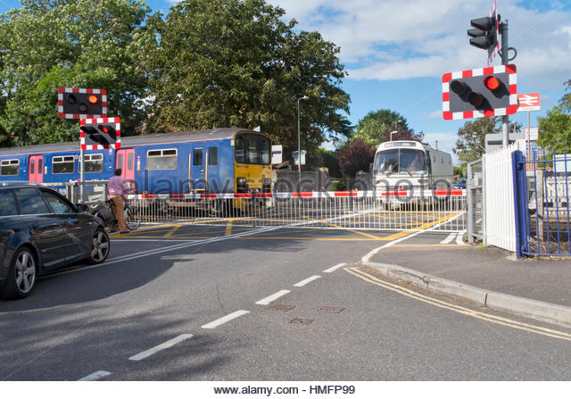 Railway train crossing road with level crossing and bus and car waiting - Stock-Bilder