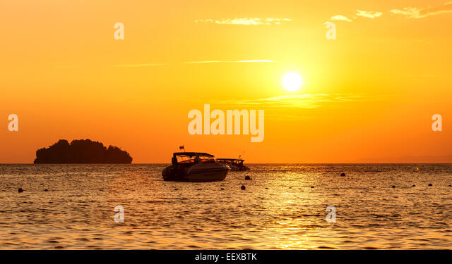 Silhouette of a little island and small boat at sunset. - Stock Image