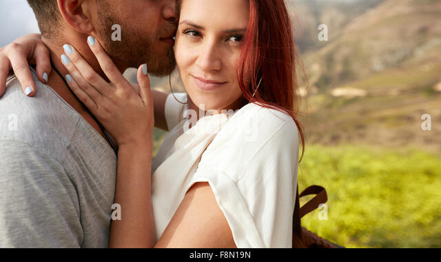 Close up shot of attractive young woman hugging her boyfriend outdoors. Romantic young couple on holiday. - Stock Image