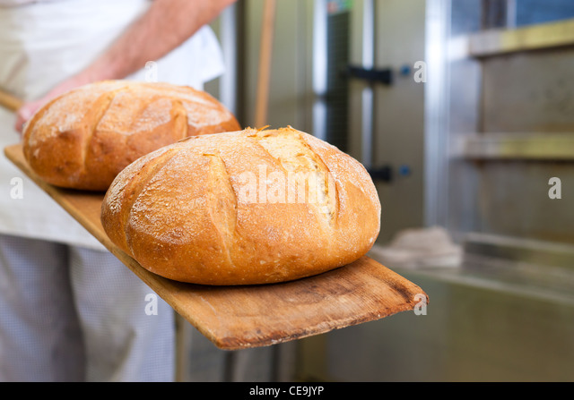 Male baker baking fresh bread in the bakehouse - Stock-Bilder