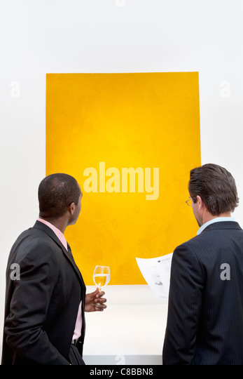 Two people looking at yellow painting on wall in art gallery - Stock Image