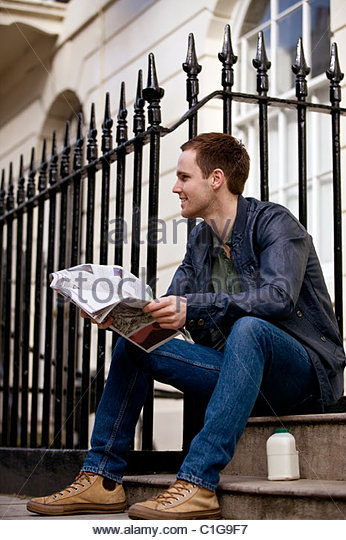 A young man sitting on a step, reading a newspaper - Stock Image