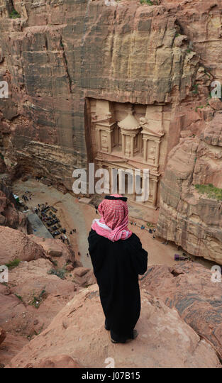 A Bedouin man looking down at the Treasury (El Khazneh) in the ancient Nabatean city of  Petra in Jordan. - Stock Image