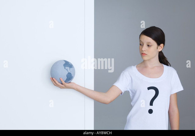 Girl wearing tee-shirt printed with question mark, looking at globe - Stock Image