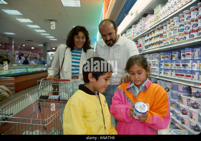 New Jersey Passaic Hispanic family grocery store dairy products children read yogurt contents - Stock Image