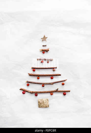 A simple Christmas tree shape made with twigs birch bark and red berries on white tissue paper - Stock Image