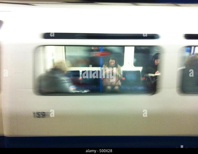 Woman using mobile phone on tube photographed through window - Stock-Bilder