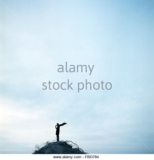 Person Standing On Hill Against Sky - Stock Image