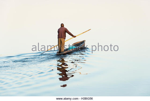 local fisherman going out fishing on his canoe on the Chobe river, Botswana - Stock Image