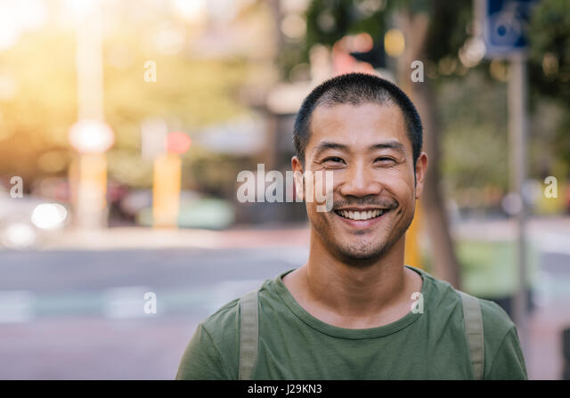 Young Asian man smiling confidently on a city street - Stock Image