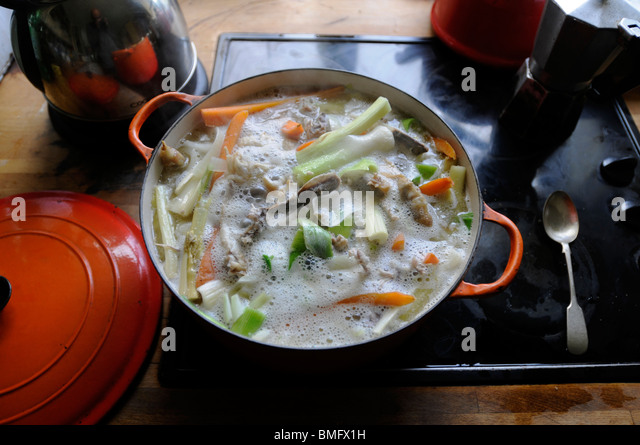 A pot of Chicken stock coming to the boil - Stock Image