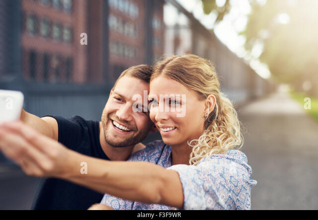 Beautiful Couple Taking a Selfie While Sitting in a Park - Stock Image