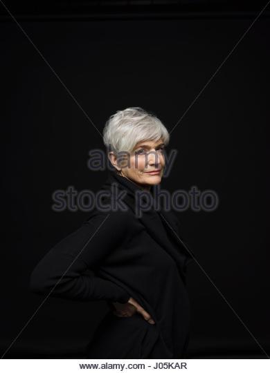Portrait confident, tough senior woman with hands on hips against black background - Stock Image