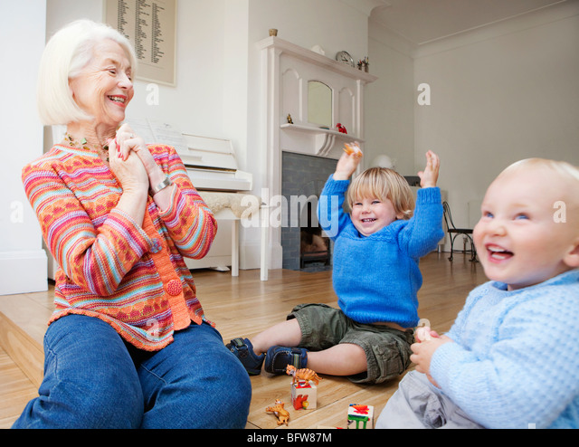 A grandmother playing with two toddlers - Stock Image