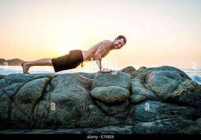 Mid adult man doing push-ups on rocks at beach - Stock Image