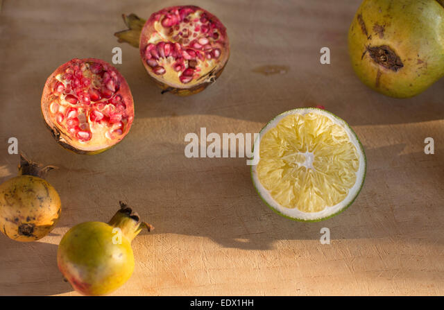 cut pomegranates in late afternoon sun with lemon against pale wood background - Stock Image