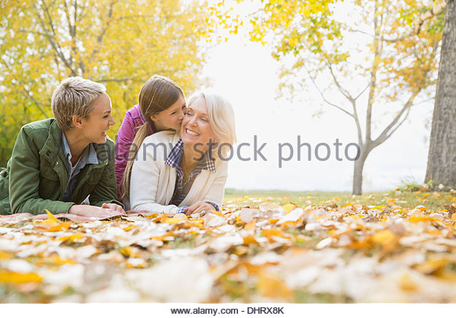 Cheerful multi generation females lying in park - Stock Image