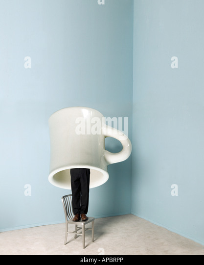business man stands or hides under giant coffee mug humor funny - Stock Image