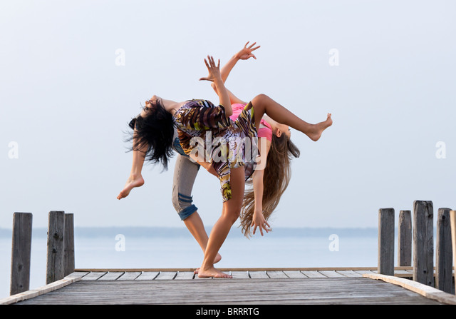 two girl  are dancing on background of water and sky - Stock Image