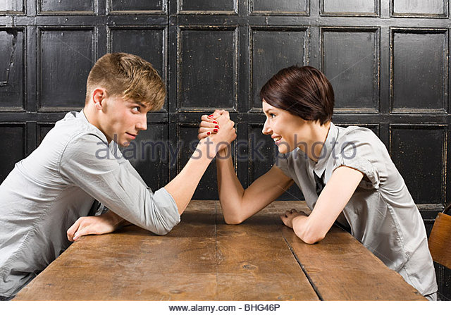 Young couple arm wrestling - Stock Image