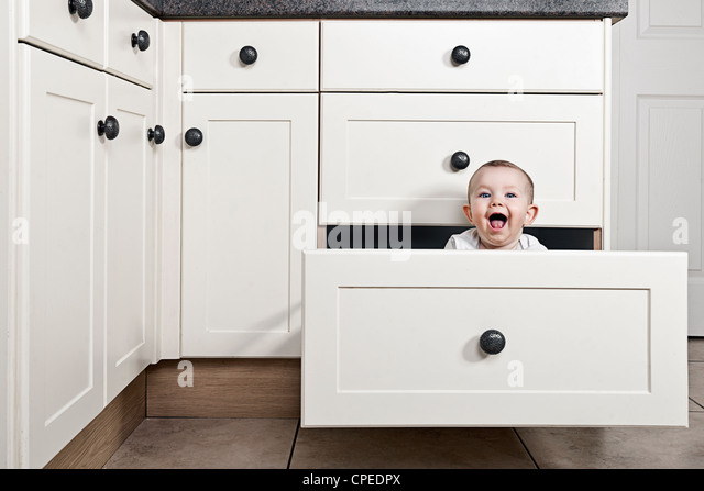 Smiling Baby Girl in Kitchen Drawer - Stock Image