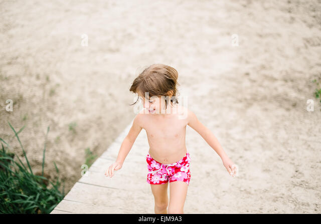 Little girl at the beach on hot summer day. Having fun during vacation. Girl walking on wooden deck at the lake - Stock-Bilder