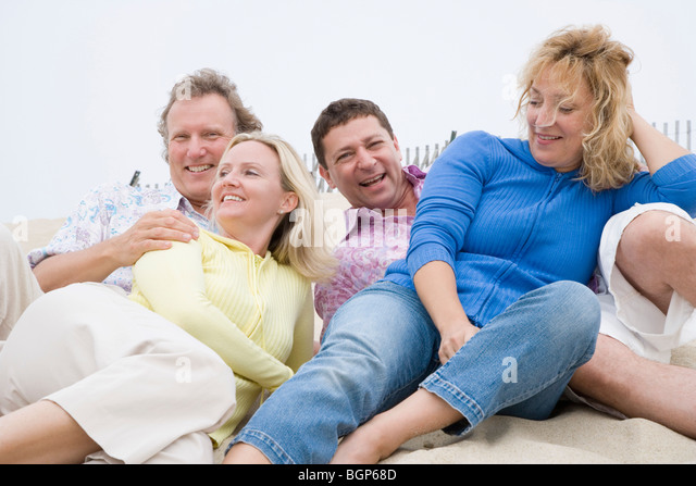 Two couples lying on the beach - Stock Image