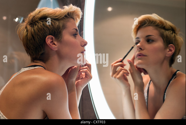 Woman applying makeup in mirror - Stock Image