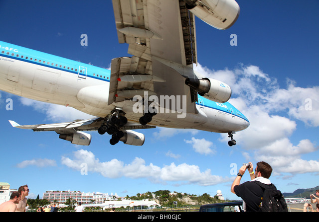 KLM 747 flying directly overhead of tourists at Maho Beach, St Maarten, Caribbean - Stock Image