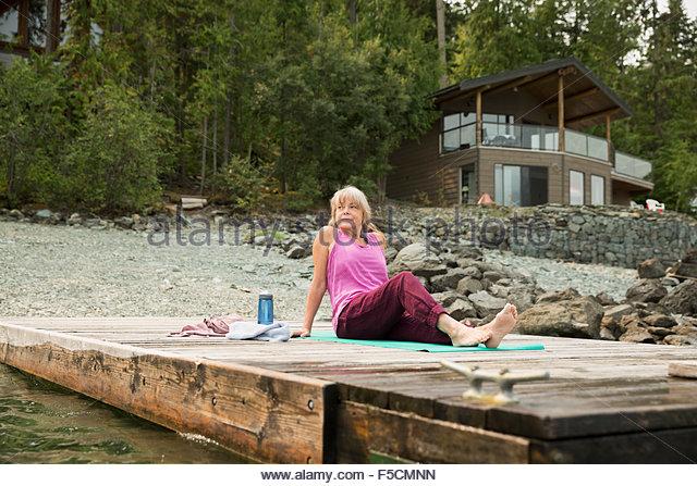 Mature woman sitting yoga mat lakeside dock - Stock Image