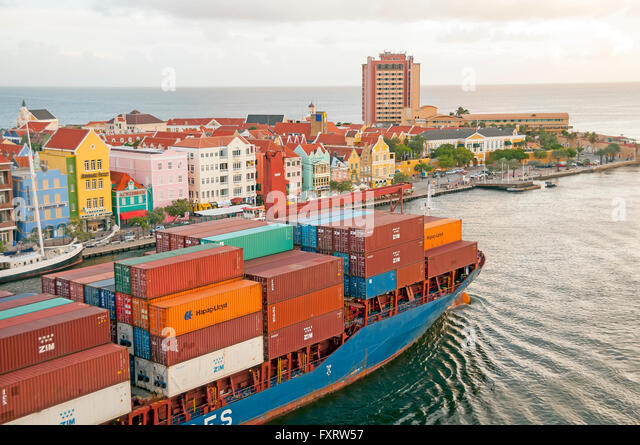 Cargo container ship travels St Anna Bay dividing Punda and Otrabanda sides of Willemstad Curacao - Stock Image