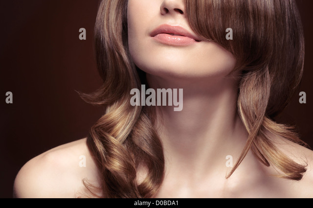 Sensual closeup portrait of a young woman mouth, neck, shoulders and wavy light brown hair. - Stock Image