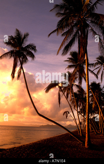 sunset on tropical beach with palms and islands in the background - Stock Image