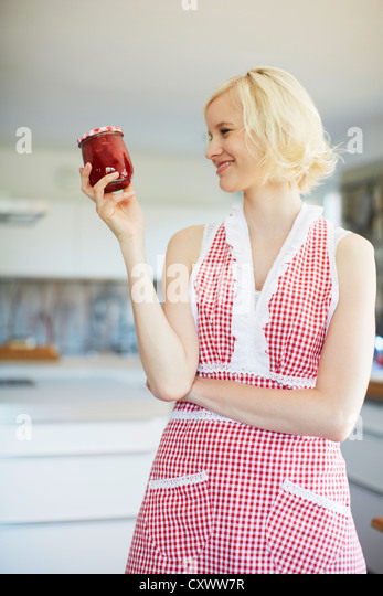 Woman holding jar of jelly in kitchen - Stock Image