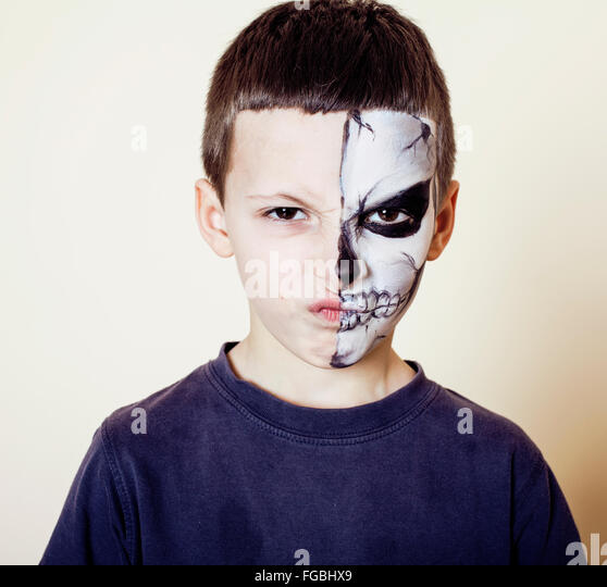 little cute boy with facepaint like skeleton to celebrate halloween - Stock Image