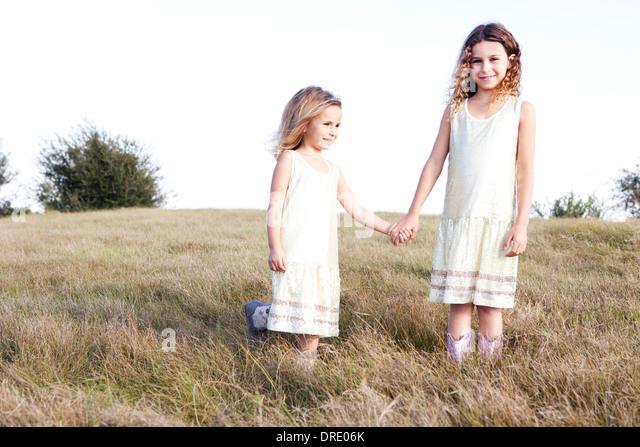 Sisters in dresses standing in field - Stock-Bilder