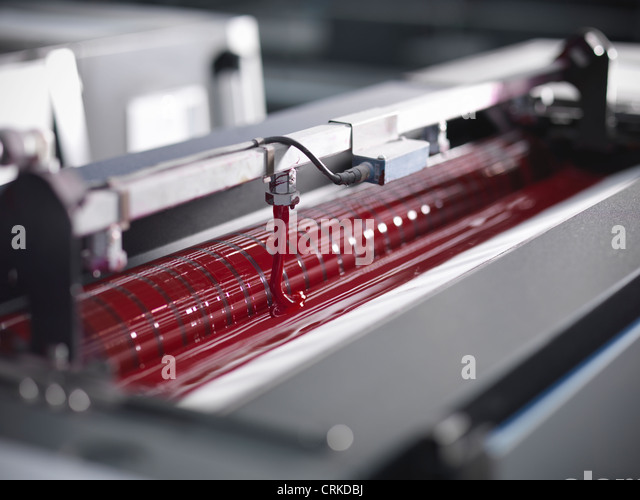 Close up of red ink in printing press - Stock Image